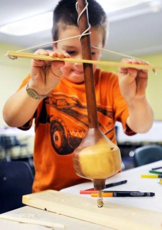Un enfant apprend à produire le feu comme le faisait l'homme durant la préhistoire